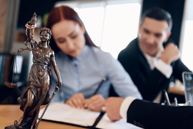 Bronzestatue von themis hält waage der gerechtigkeit im amt.