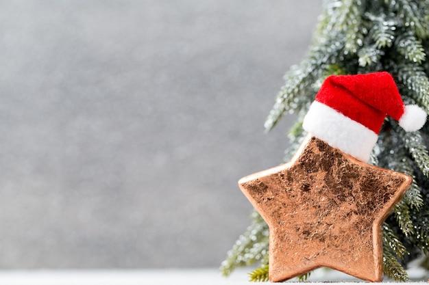 Bronzestern und weihnachtsmütze. weihnachtsdekoration hintergrund