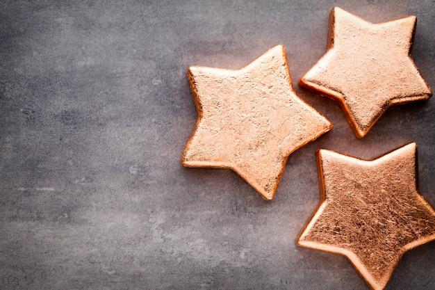 Bronzestern. weihnachtsmuster. hintergrund auf der grauen farbe.