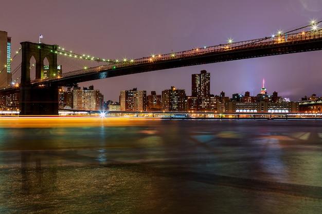 Brooklyn bridge in der dämmerung von new york city aus gesehen.