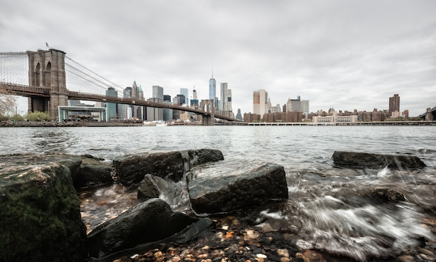 Brooklyn bridge mit felsen am ufer des east river