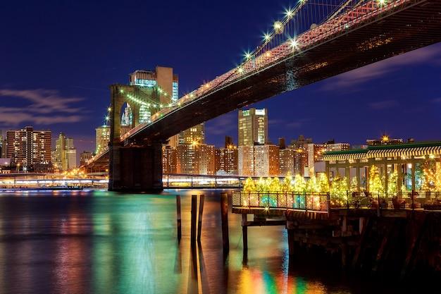 Brooklyn bridge nahaufnahme über east river in der nacht in new york city manhattan mit lichtern und reflexionen.