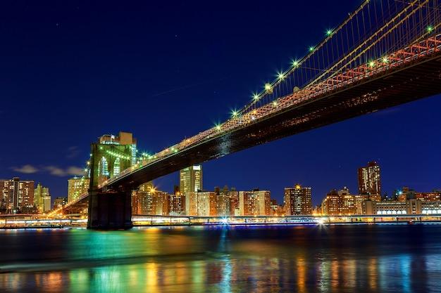 Brooklyn bridge über den east river bei nacht in new york city manhattan mit lichtern und reflexionen.