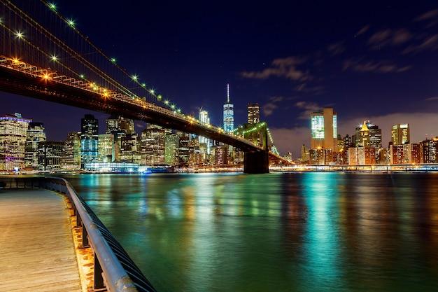 Brooklyn bridge über den east river bei nacht in new york city