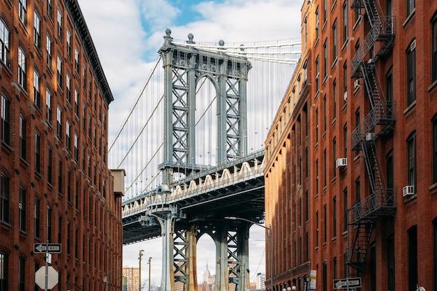 Brooklyn bridge zwischen zwei schönen braunen gebäuden bei sonnenuntergang gesehen - ansicht von unten