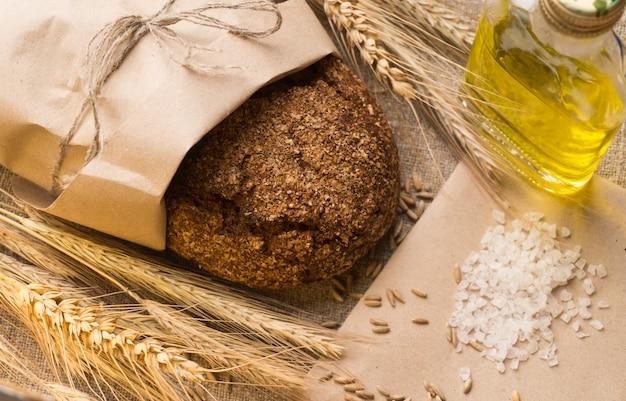 Brot, ähren, getreide und pflanzenöl auf sackleinen.