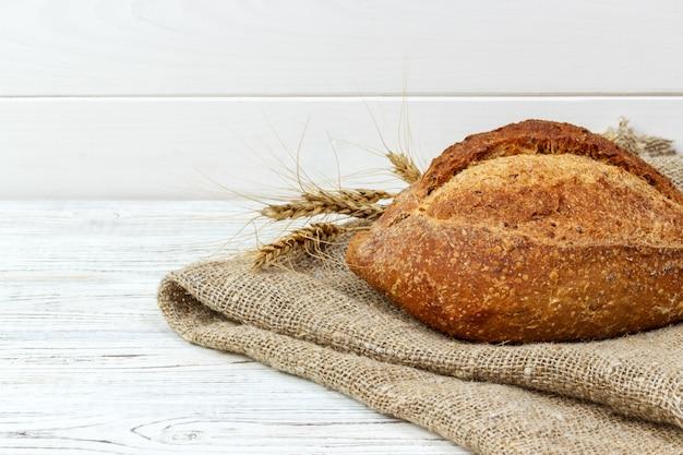 Brot auf dem tisch. backen des teigs auf einem weißen hölzernen hintergrund