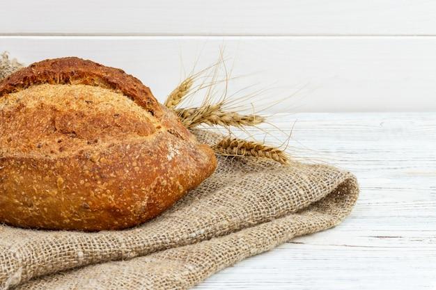 Brot auf dem tisch, selbst gemachtes brot mit weizen auf einem hölzernen hintergrund