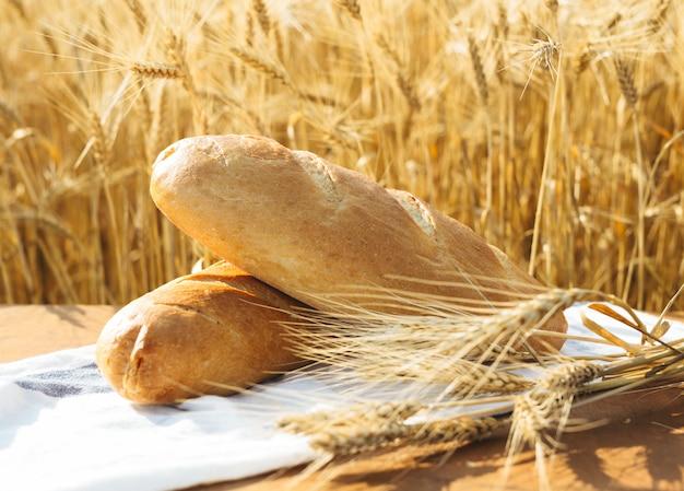 Brot auf dem tisch und weizen auf dem gebiet des weizens und des sonnigen tages