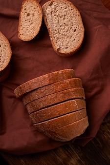 Brot auf dunklem holztisch und brauner serviette. brotscheiben und -krumen angesehen von oben.