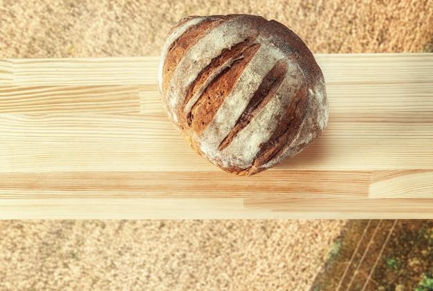 Brot auf einem holzbrett auf dem hintergrund einer roggenfeld-draufsicht
