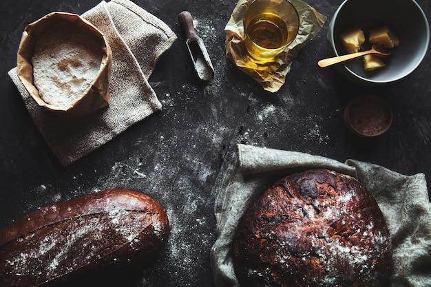 Brot auf einem schwarzen hintergrund. hausgemachtes gebäck mit zutaten.