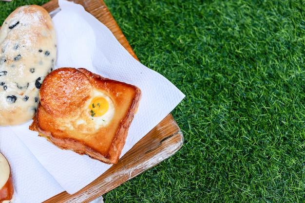 Brot auf hölzerner platte und grünem gras