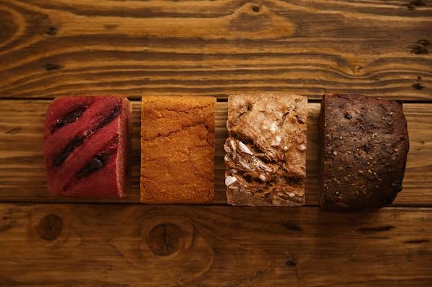 Brot aus verschiedenen stücken gemischter hausgemachter brote, die auf einem rustikalen tisch als muster zum verkauf angeboten werden. hergestellt aus süßkartoffeln