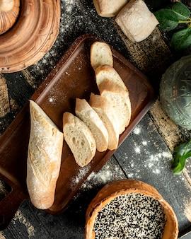 Brot baguette an bord mit sesam und brötchen auf dem tisch