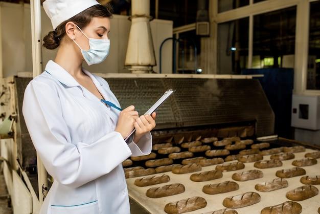 Brot. brotproduktionslinie. frau in uniform. hygienekontrolle.