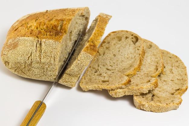 Brot, brotscheiben und ein messer auf weißem grund