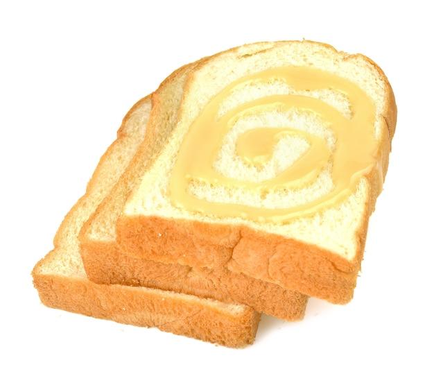 Brot, butter, sahne, gesüßte kondensmilch auf weiß