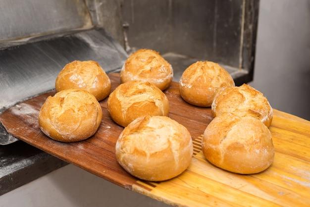 Brot gerade aus dem ofen. frisch gebackenes brot, herausgenommen mit einer schaufel.