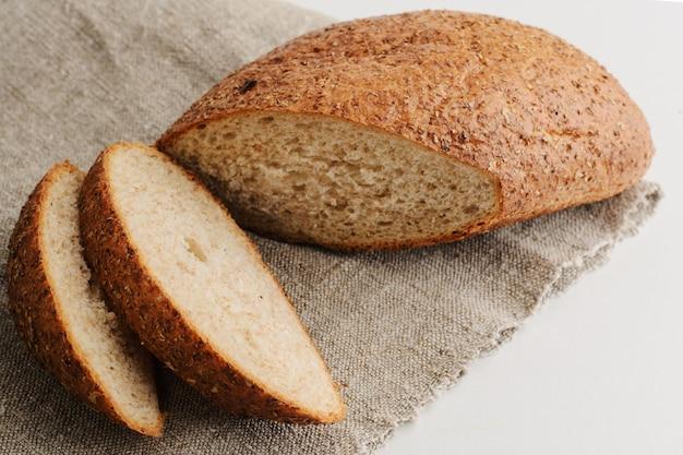 Brot, geschnitten im sackleinen auf weißem hintergrund