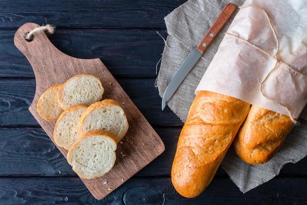 Brot in backpapier und schneidebrett