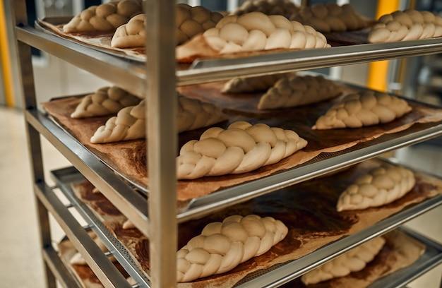 Brot in den regalen wird zum backen im ofen vorbereitet. herstellung von backwaren.