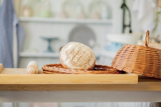 Brot in der nähe eines weidenkorbs auf einem tisch in einer rustikalen küche. komposition in der küche im fotostudio.