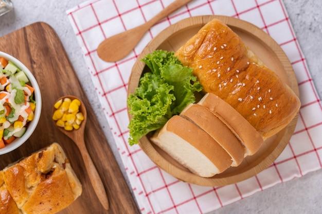 Brot in einem holztablett auf einem rot-weißen tuch.