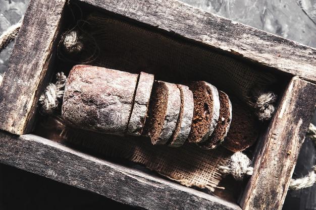 Brot in einer alten holzkiste, die bereits in stücke geschnitten wurde. lebensmittel