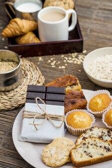 Brot, kekse, cupcake und dunkle schokolade auf dem teller