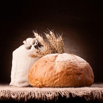 Brot, mehlsack und ohrenbündel stillleben auf rustikalem tisch