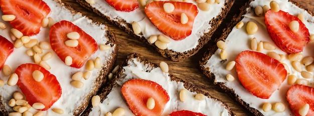 Brot mit erdbeeren, pinienkernen und frischkäse auf holz