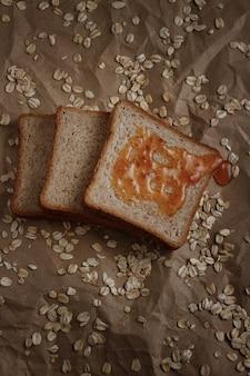 Brot mit marmelade auf einer braunen fläche und haferflocken