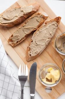 Brot mit pastete und butter auf einem textilhintergrund.
