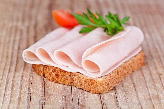Brot mit schinkenscheiben, frischen tomaten und petersilie