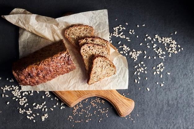 Brot mit sonnenblumen- und leinsamen auf einem holzbrett auf schwarzem hintergrund. flache lage, ansicht von oben, kopierraum