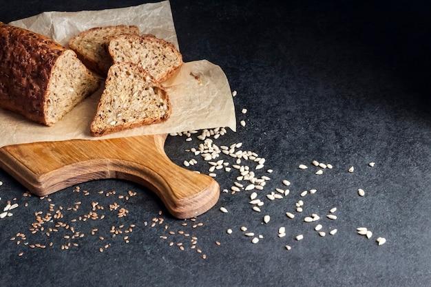 Brot mit sonnenblumen- und leinsamen auf einem holzbrett auf schwarzem hintergrund