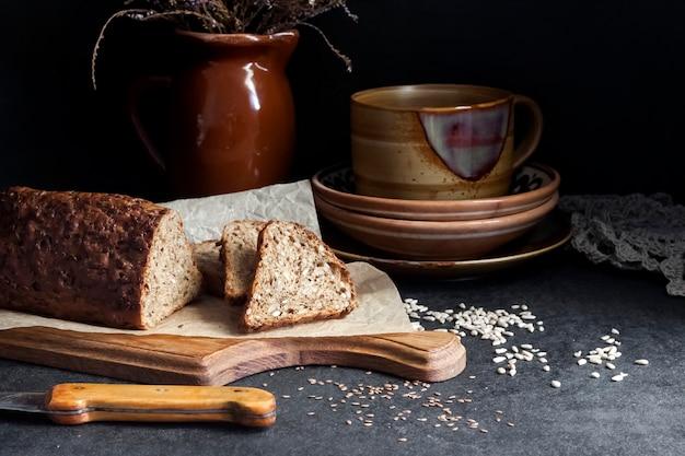 Brot mit sonnenblumen- und leinsamen auf einem holzbrett keramikgeschirr im hintergrund