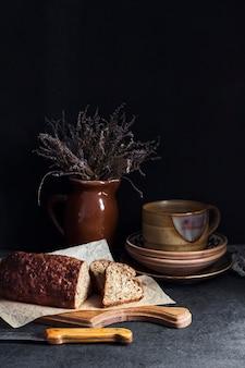 Brot mit sonnenblumen- und leinsamen auf einem holzbrett. keramikgeschirr im hintergrund.