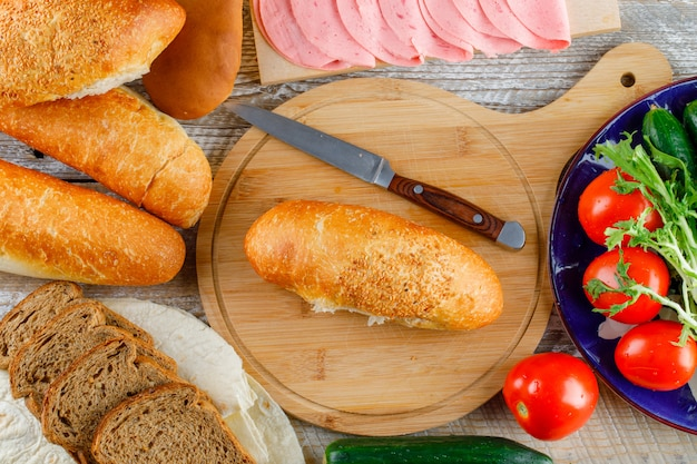 Brot mit tomaten, gurken, messer, wurst, gemüse flach auf holz und schneidebrett liegen