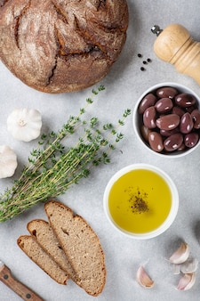 Brot, olivenöl, kalamata-oliven, knoblauch und kräuter auf blauem hintergrund, ansicht von oben