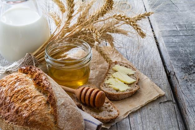 Brot, roggen, weizen, honig, rustikaler hölzerner hintergrund der milch