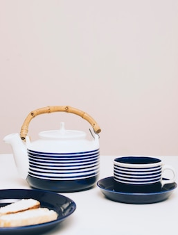 Brot; teekanne und tasse kaffee auf dem schreibtisch gegen farbigen hintergrund