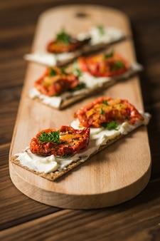 Brot toast mit frischkäse und sonnengetrockneten tomaten auf einem schneidebrett.