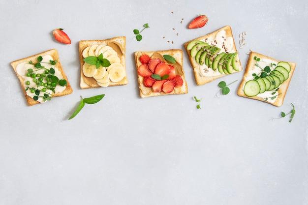 Brot toast mit obst und gemüse. banane, erdbeeren, avocado, gurke, erbsen. set toast zum frühstück. draufsicht, kopierraum.