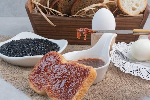 Brot und eier mit marmelade auf sackleinen.