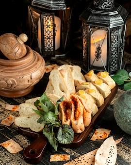 Brot und gebäck mit basilikum und kirschtomate an bord