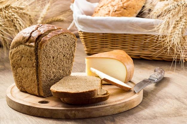 Brot und käse in scheiben geschnitten zwischen den broten in einem weidenkorb mit weizenähren