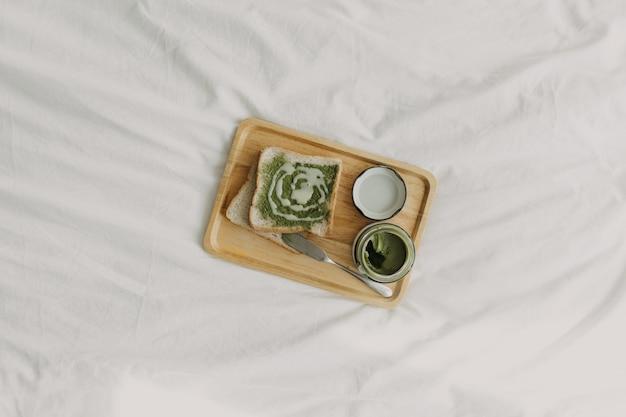 Brot und matcha-marmelade des grünen tees auf hölzerner platte.