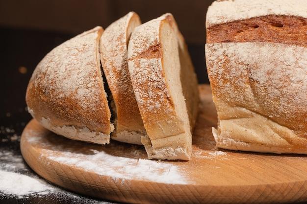 Brot und mehl auf einem holzbrett